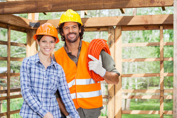 Happy Architect Standing With Worker In Incomplete Wooden Cabin