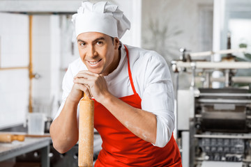 Portrait Of Confident Chef Leaning On Rolling Pin