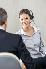 Young Female Customer Service Executive Looking At Manager