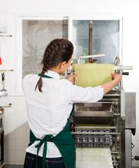 Female Chef Processing Pasta Sheet In Machine