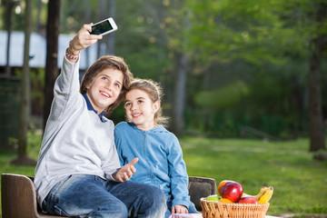 Siblings Taking Selfportrait Through Smartphone At Campsite