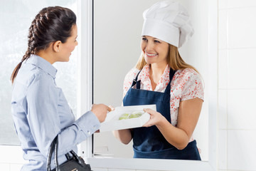 Woman Buying Ravioli Pasta Packet From Female Chef