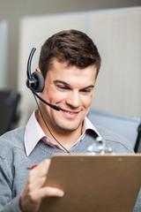 Smiling Customer Service Representative Wearing Headset While Ho