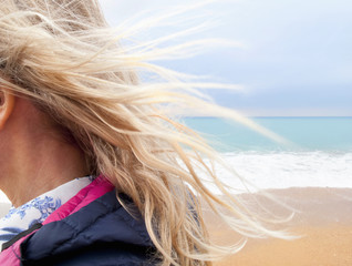 Blond hair blowing in breeze on beach