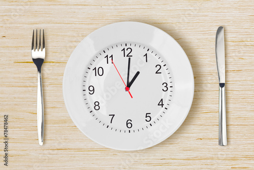 Dinner plate with clock face on wooden table - 78478462