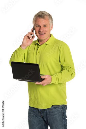 canvas print picture Mann mit Laptop telefoniert mit Smartphone