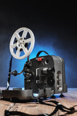 Movie projector with the film on the wooden floor.