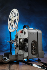 Movie projector with the film on the wooden floor