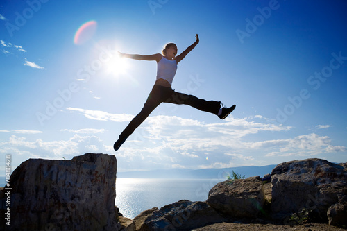 Beautiful young woman jumping from the rock - 78480428