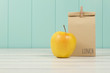 An apple and a paper bag with lunch. Vintage Style.