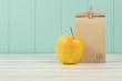 Leinwanddruck Bild - An apple and a paper bag with lunch. Vintage Style.