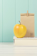 An apple and a paper bag with lunch on a book. Vintage Style. - 78480873