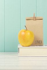 An apple and a paper bag with lunch on a book. Vintage Style.