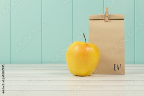 Leinwanddruck Bild An apple and a paper bag with lunch. Vintage Style.