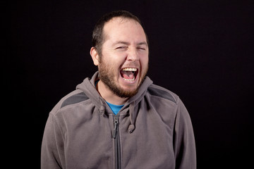 young man laughing isolated on black background