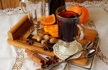 A glass of hot mulled wine and spices.