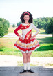 Young woman in irish dance dress and wig posing outdoor