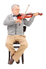 Senior gentleman playing a violin seated on a chair