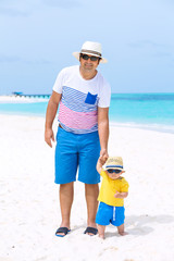 Father and son on white sandy beach on Maldives