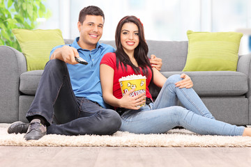 Couple watching TV and eating popcorn at home