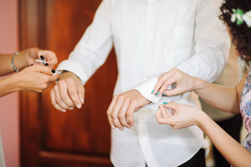 A groom fastening a cuff-link before getting married.