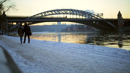 Man and woman walking in the evening by river