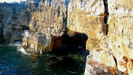 Waves coming through a natural hole in a cliff, Boca do inferno