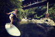 young girl surfing the wave of the river on a surfboard