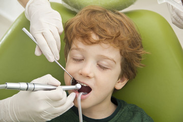 close up of boy having his teeth examined by dentist