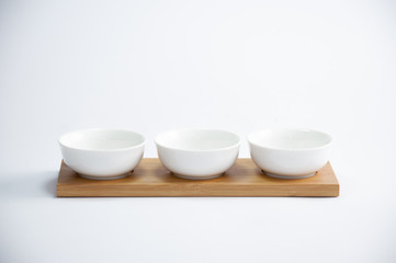trio of white coffee cups arranged in a row on a wooden tray