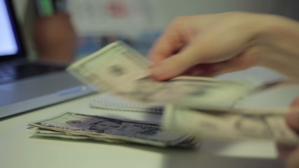Woman counting money and write result to notebook