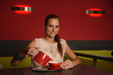 Pretty young woman drinks tea in bar