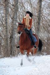 Woman horseback riding on the winter park way