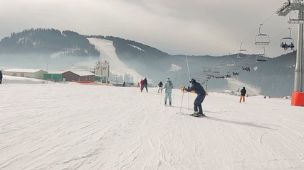 Skiers ride on the ski slopes.