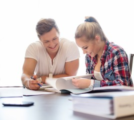 Young students couple preparing for exams behind table