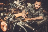 Mechanic with cafe-racer motorcycle  in custom garage