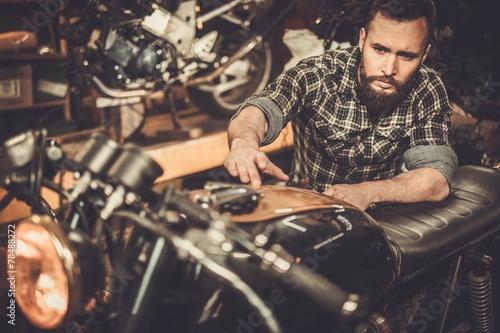 Leinwanddruck Bild Mechanic with cafe-racer motorcycle  in custom garage