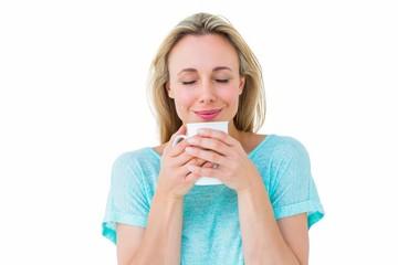 Cheerful blonde holding mug of hot drinking