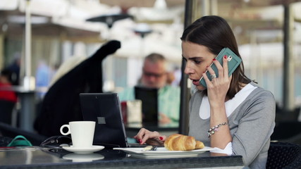 Young businesswoman with laptop and cellphone sitting in cafe