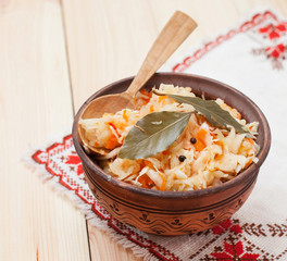 sauerkraut in ceramic bowl with wooden spoon on wooden table wit