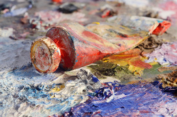 Closeup of old oil paint tube with red colour lying on palette