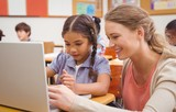Fototapety Cute pupil using computer with teacher