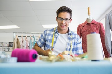 Fashion student cutting fabric with pair of scissors