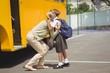 Mother hugging her daughter by school bus - 78492664