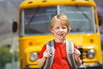 Cute pupil smiling at camera by the school bus