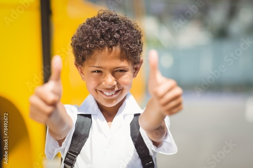 Cute pupil smiling at camera by the school bus - 78492672