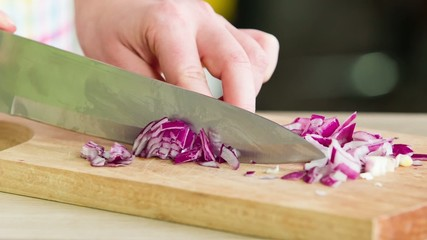 Woman Slicing Red Onion On Wooden Board