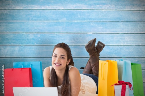 canvas print picture Composite image of brunette lying and using her laptop