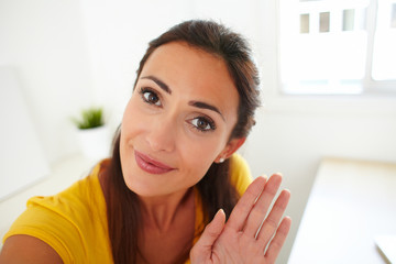 Latin lady greeting a person on webcam