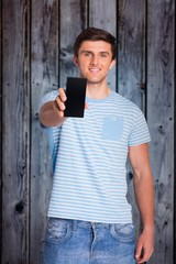Composite image of young man showing phone to camera